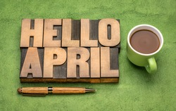 Hello April word abstract in vintage letterpress wood type with a cup of coffee against green handmade paper, cheerful greetings