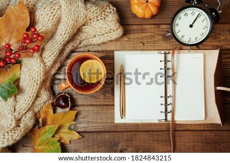 Hello autumn. autumn background with notebook, rowan, chestnuts, leaves, tea and lemon on wooden planks. Foto stock ©
