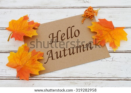 Hello Autumn Card, A brown card with words Hello Autumn over a distressed wood background with Autumn Leaves