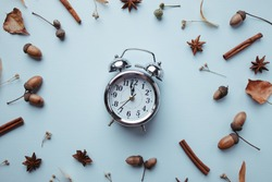 Hello autumn, season change time, thanksgiving day, seasonal holidays concept. Fall composition, background made of dried leaves, clock, pine cones and acorns on blue