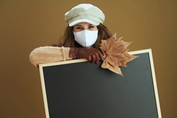 Hello autumn. smiling elegant middle aged housewife in scarf with white medical mask and yellow autumn maple leaves showing blank black board on bronze background.
