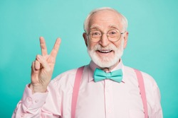 Hello. Closeup photo of amazing stylish clothes grandpa showing v-sign symbol greets friends wear specs pink shirt suspenders bow tie isolated bright teal color background