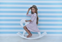 Hello! Cute little girl adjusting her hat and looking at camera with smile while sitting on the toy horse