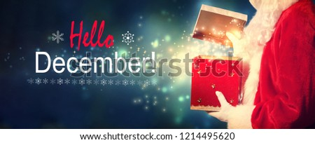 Hello December message with Santa opening a gift box on a shiny light background