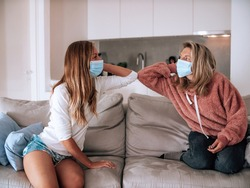 Hello elbows no contact- Two friends wearing medical face mask on sofa at home. Social distancing with friends and family for safety measures to prevent Covid19 virus to spread.