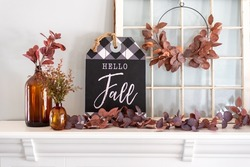 Hello fall sign and amber glass bottles on a white mantel decorated for Fall