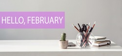 Hello February - text on the background of the office table. Business concept