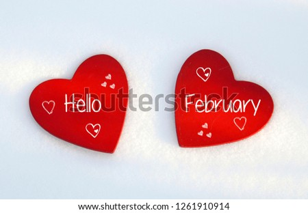 Hello February.Two red wooden hearts on natural white snow background. Winter holidays or Valentines Day concept.Selective focus.