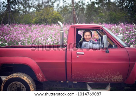 Hello! gardener woman smiling and shows gesture of greeting in red pickup trucks. Asian girl farmers are driving pickup trucks in the cosmos flower garden. Gardening concept.