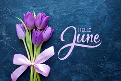 Hello June hand lettering inscription with summer tulip flowers on blue background.
