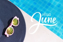 Hello June hand lettering, sun hat and sun glasses near the swimming pool.