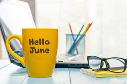 Hello June - inscription at yellow morning coffee or tea cup at business office background. First summer day, Calendar concept