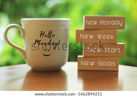 Hello Monday concept with inspirational quote on wooden blocks - New Monday. New Week, New Start. New Goals. And a smiling face on a white morning cup of coffee or tea.