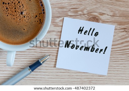 Hello November. hand drawn lettering on notepad at the table with morning coffee cup. Top view