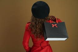 Hello november. Seen from behind woman in red coat and black beret with leather gloves and paper shopping bag isolated on bronze background.
