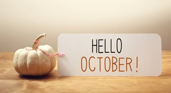 Hello October message with a white small pumpkin