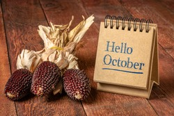 Hello October welcome note  - handwriting in a spiral sketchbook on a rustic wooden table with decorative strawberry corn, season and calendar concept