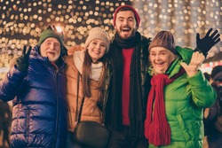 Hello. Photo of full family four members x-mas meeting gathering, cuddle show v-sign greet friend wave hand wear hat scarf coat gloves multi-generation evening street garland fair outdoors