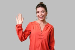 Hello! Portrait of charming woman with bun hairstyle, big earrings and in red blouse standing, waving hand and saying Hi to camera with toothy smile. indoor studio shot isolated on gray background