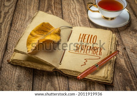 Hello September handwriting in a retro journal with decked edge handmade paper pages and a stylish pen on a rustic wooden table with a cup of tea, fall and journaling concept