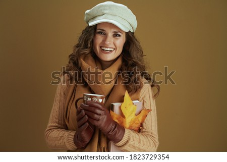 Hello september. Portrait of happy modern female in scarf with yellow autumn maple leaf, book, leather gloves and cup against beige background. Stock photo ©
