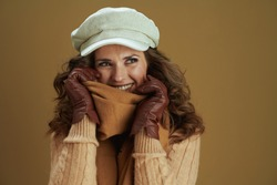 Hello september. smiling elegant 40 years old housewife in scarf with leather gloves looking at copy space isolated on beige background.