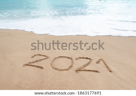 Hello 2021 sign on the sandy beach with soft wave of white foam. Welcoming 2021 with new resolutions, dreams concept.