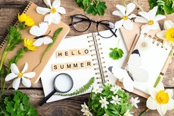 Hello summer card, open notebook, flowers and herbs, butterfly, pen, magnifier, glasses on wooden background. Office desk table. Studying, education, botanic, summer, zero waste, ecology concept