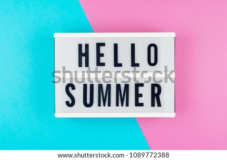 Hello Summer - text on a display lightbox on blue and pink bright background.