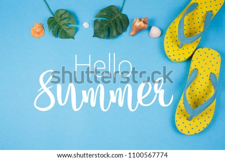 Hello Summer text on blue background, Yellow sandals with green tropical palm leaf and shell. Beach accessories