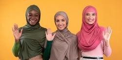 Hello. Three Cheerful Muslim Ladies In Hijab Waving Hands In Greeting Gesture Smiling To Camera Standing Over Yellow Studio Background. Arabic Women Gesturing Hi Or Goodbye. Panorama