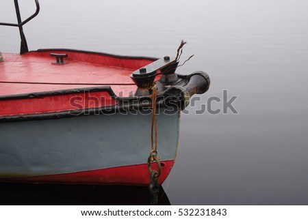Helm of an anchored antique fishing boat in early morning fog in early morning fog in Grandes-Piles, Quebec, Canada #532231843
