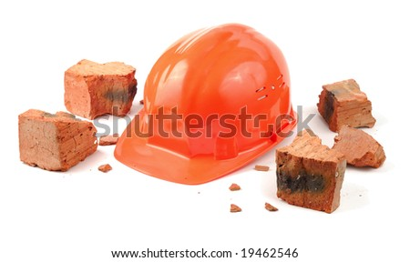 Helmet and pieces of broken brick isolated over white