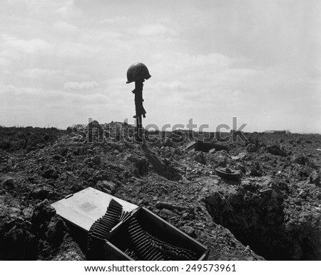 Helmet and rifle monument to a dead U.S. soldier on a shell-blasted beach of France. He was killed on D-Day during the Normandy landings, June 6, 1944, World War 2.