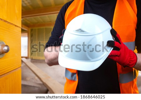 Helmet construction. Builder holds a protective helmet in his hands. Concept - sale of construction helmets. Selling uniforms for builders. Overalls for the builder. Man in a builder uniform