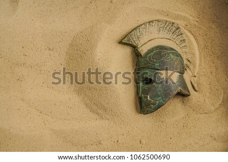helmet of ancient warriors in sand. Roman Legionar's helmet with the Iroquois.Archeology and paleontology concept archaeological excavation ancient history achaeologists unearth ancient artifacts
