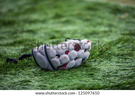 helmet rugby player thrown on the green grass - stock photo