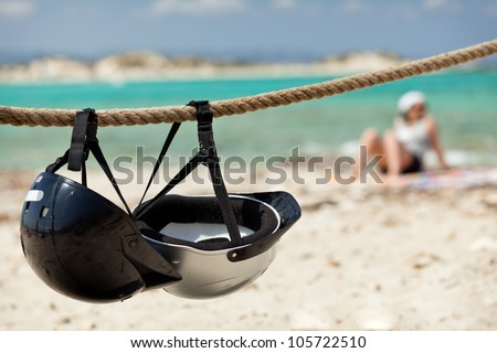 Helmets on the beach.  Young woman relaxing on the beach.
