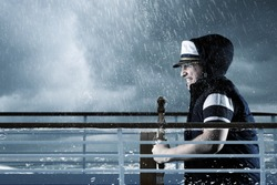 helmsman with vest and cap struggle against storm in front of stormy sea