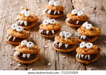 Heloween dessert: funny monsters made of biscuits with chocolate and marshmelow close-up on the table. horizontal
