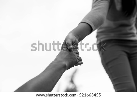 Help Concept Young girl Hands reaching out to help old woman in black and white #521663455