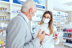 Help from a pharmacist. A female pharmacist with glasses holds medicine boxes and instructions for use. She looks at the man who is explaining something else. They both wear protective masks