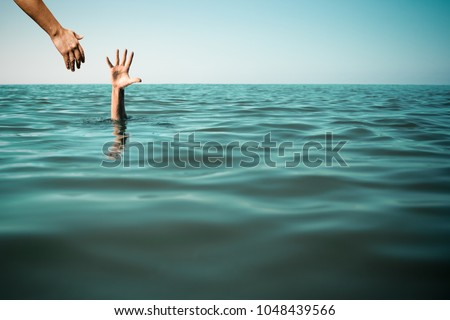 Help hand for drowning man life saving in sea or ocean. Stock photo ©