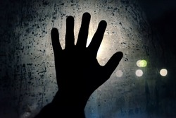 Help me. A hand calling for help on the foggy night glass window. Symbol of helplessness