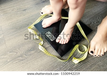 Help your child to have a healthy diet and lifestyle, with obese kid feet on weight scale, under the supervision of the mother