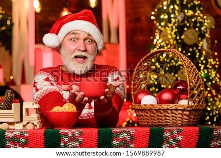 Help yourself. Hot beverage. Christmas cocoa recipe. Garland lights cozy atmosphere. Cozy home. Senior man Santa claus drinking tea. New year. Grandpa with mug. Christmas eve treats. Cozy interior. #1569889987