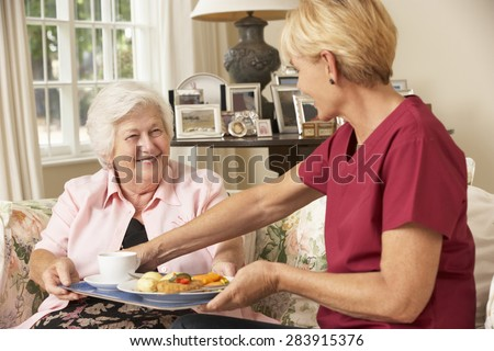 Helper Serving Senior Woman With Meal In Care Home ストックフォト ©