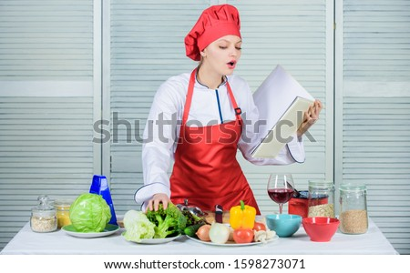 Helpful culinary book. Woman chef cooking food. Culinary concept. Amateur cook read book recipes. Girl learn recipe. Book by famous chef. Improve cooking skill. Book recipes. According to recipe.