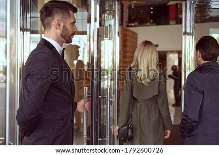 Helpful doorman wearing uniform welcoming people inside the hotel while holding the entrance door open Сток-фото ©