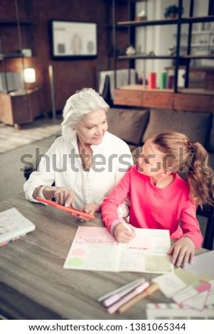 Helpful granny. Helpful loving granny assisting her cute granddaughter making homework